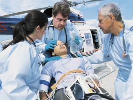 A medical team greets a patient airlifted by helicopter.
