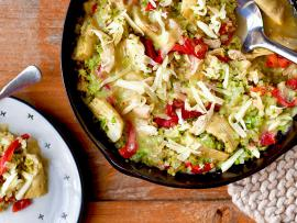 broccoli rice with chicken, peppers and artichoke hearts in a cast iron skillet