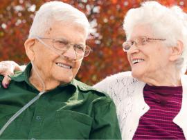 elderly man with oxygen sitting with his elderly wife enjoying the day