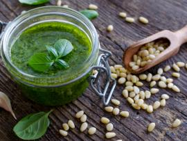 A jar of homemade basil pesto on a rustic wood background, surrounded by garlic cloves and pine nuts.