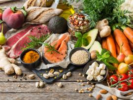 A spread of healthy food, including fresh vegetables, fresh fish, nuts, beans and whole grains.
