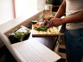 Man looks up a recipe on his laptop while cooking healthy food in his kitchen.
