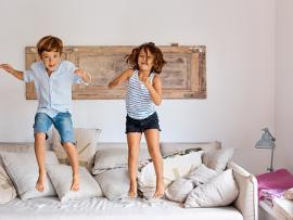 Brother and sister jumping on a sofa.