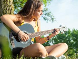 A teenager strums her guitar.