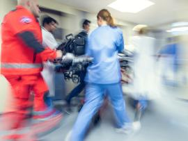 Medics push patient in bed down hallway_3 tips to prevent falls