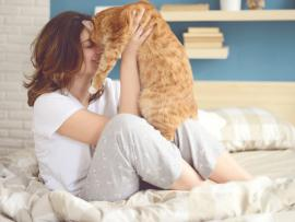 woman holding cat in bed