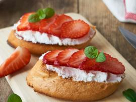 Sliced strawberries on top of ricotta toast, arranged on a wooden plank.