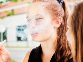 A teen girl smokes an e-cigarette.