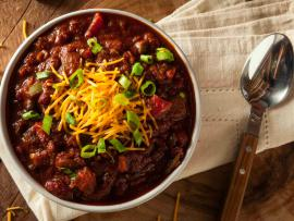 a hot bowl of vegetarian chili with chesse and sliced green onions sprinkled on top