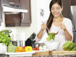 woman fixing a healthy salad in her kitchen