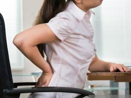 A woman at work rubs her sore back.
