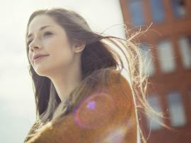 Woman standing outside with hair blowing in the wind_The power of mindfulness