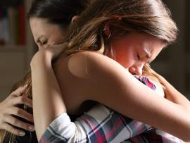 a woman hugging her teenage daughter who is struggling with grief