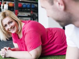 woman in pink shirt doing plank pose in gym with personal trainer