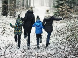 active family taking a hike in the cold weather after a light snow