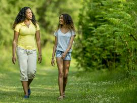 African American mom and daughter walking in woods and smiling