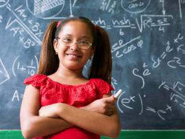 african american girl standing in front of a chalk board with math on it at school