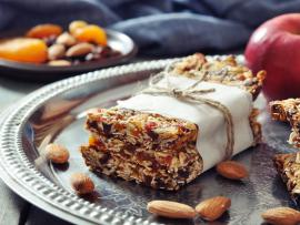 homemade apricot nut granola bars on platter with almonds and apple