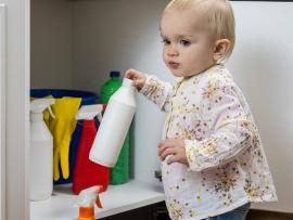 v=baby holding a bottle of cleaning solution