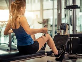 woman doing seated rows on machine at the gym
