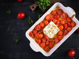 A white ceramic baking dish filled with tomatoes topped with soft cheese, against a dark slate background.