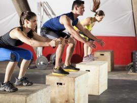 men and women doing box jumps in the gym