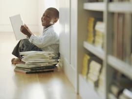 boy reading books laughing