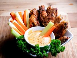 A bowl of buffalo dip, surrounded by carrot and celery sticks, wings and fresh parsley, sits on a wooden cutting board.