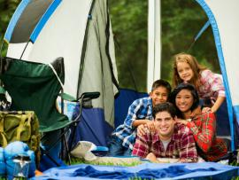 family sitting outside tent spending time together