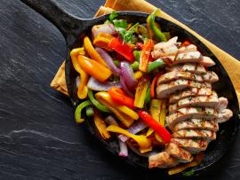 sizzling hot pan of chicken fajitas with peppers and onions