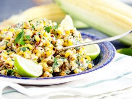 Plate of coconut corn salad served with fresh lime wedges, with a fresh ear of corn in the background.