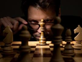 man with glasses in low light contemplating wooden chess board