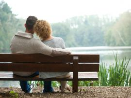 couple sitting on bench and looking out at lake