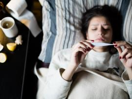 sick woman in bed holding thermometer with tea and lemons on the nightstand