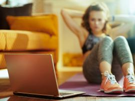 closeup of open laptop with woman working out in background