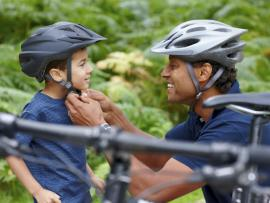 dad putting bike helmet on young son