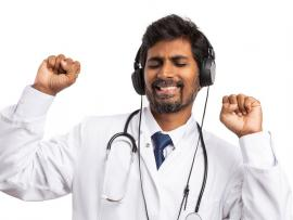 doctor with headphones on dancing with eyes closed