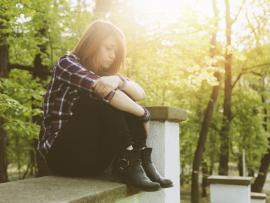 depressed teen sitting on a curb.