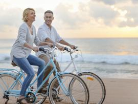 couple riding bikes on the beach