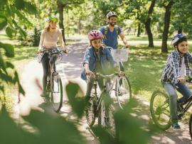 family riding bikes together on a green way