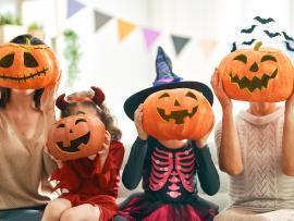 Family holding carved Halloween pumpkin heads