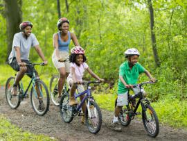 african american family enjoying a bike ride on wooded path