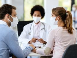 couple in surgical masks at fertility clinic facing doctor also in a mask