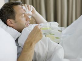 man laying in bed with flu