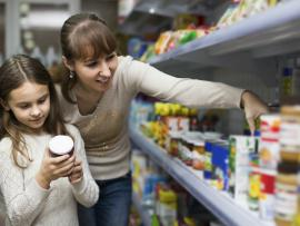Mother and daughter grocery shopping looking at food labels