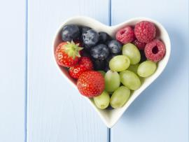 fresh strawberries, blueberries, raspberries and grapes in a bowl.