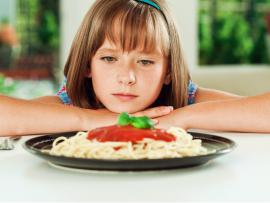 tween girl not eating her plate of spaghetti