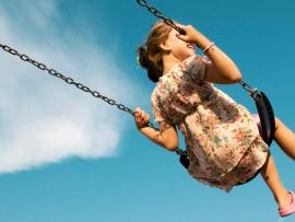 child in dress swinging high viewed from behind with blue sky and a single cloud beyond her