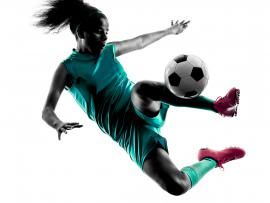 teenage girls kicking a soccer ball