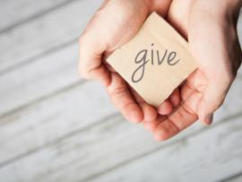 hands holding the sign that says give